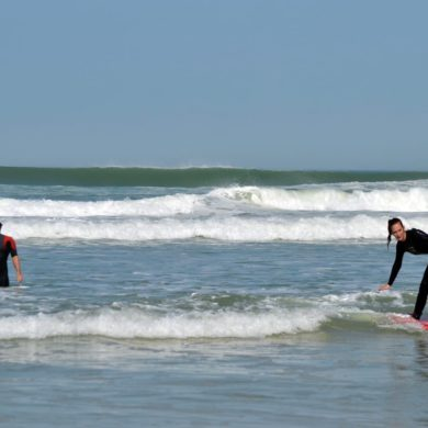 Surfeuse en plein cours de surf à Lacanau avec Magic Surf School